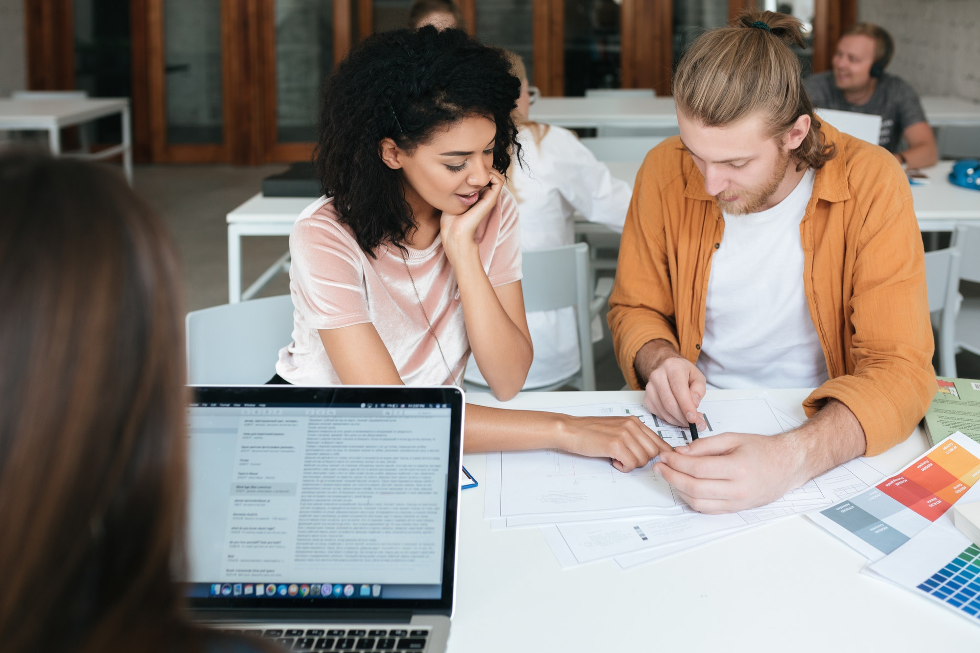 Young man and girl working and making notes together in office