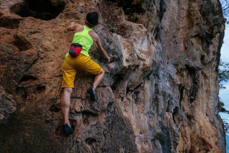 Woman climbing rock on cliff